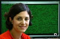 Kaye Award winner Naama Elefant with a computer screen showing a DNA sequence in the background (Credit: Hebrew University / Sasson Tiram).