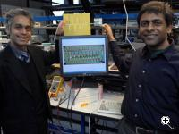 Sarpeshkar and Mandal display their chip next to a wiring diagram (Credit: Donna Coveney/MIT)
