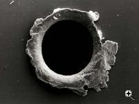 View of an orbital debris hole made in the panel of the Solar Max experiment (Credit: NASA)